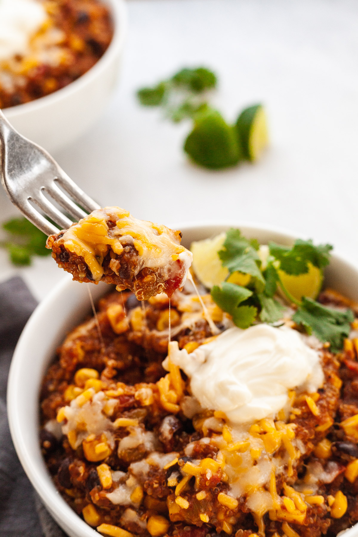 close up image of quinoa enchilada in white bowl with fork scooping out casserole