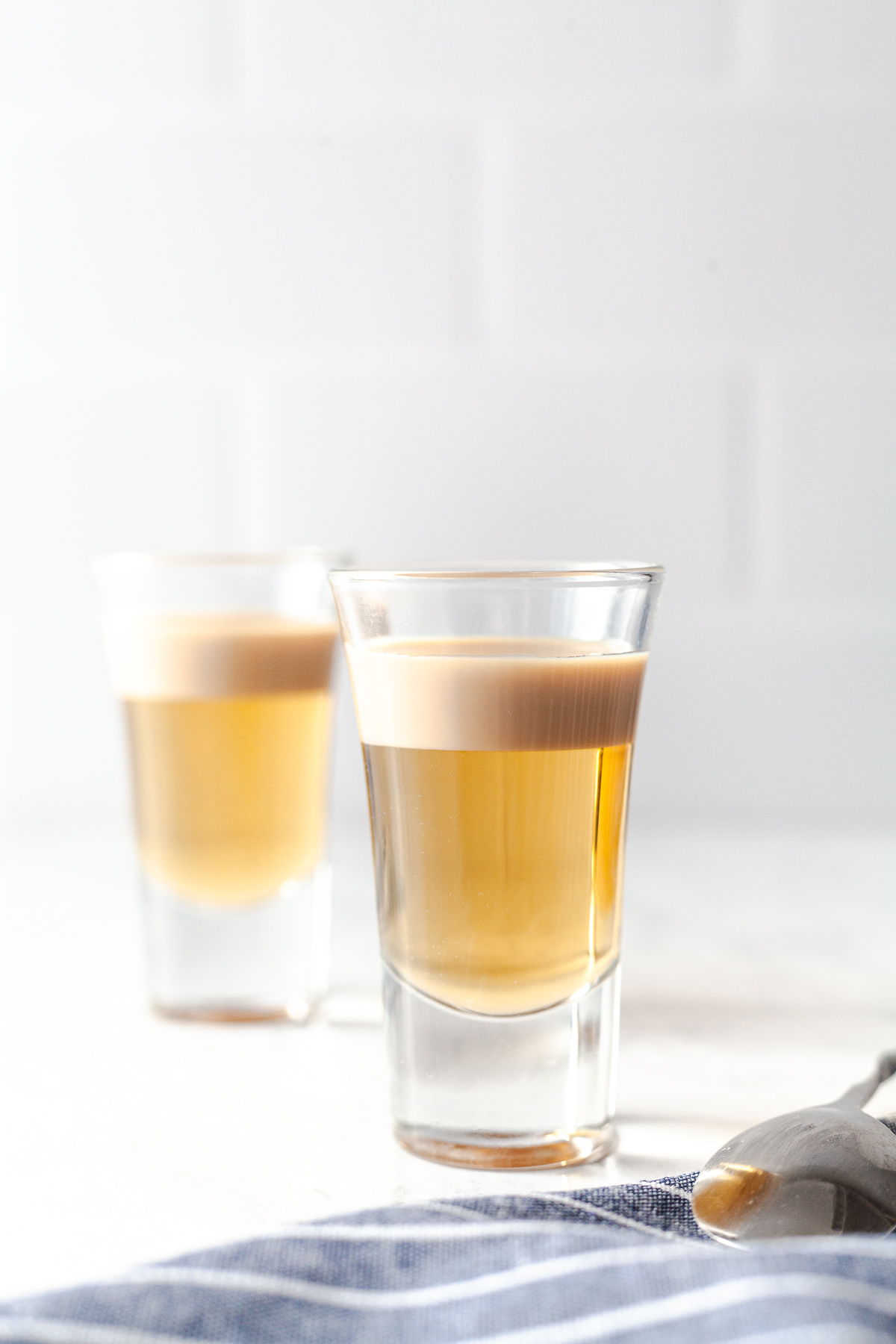 side image of two shot glasses with butterscotch schnapps and irish cream