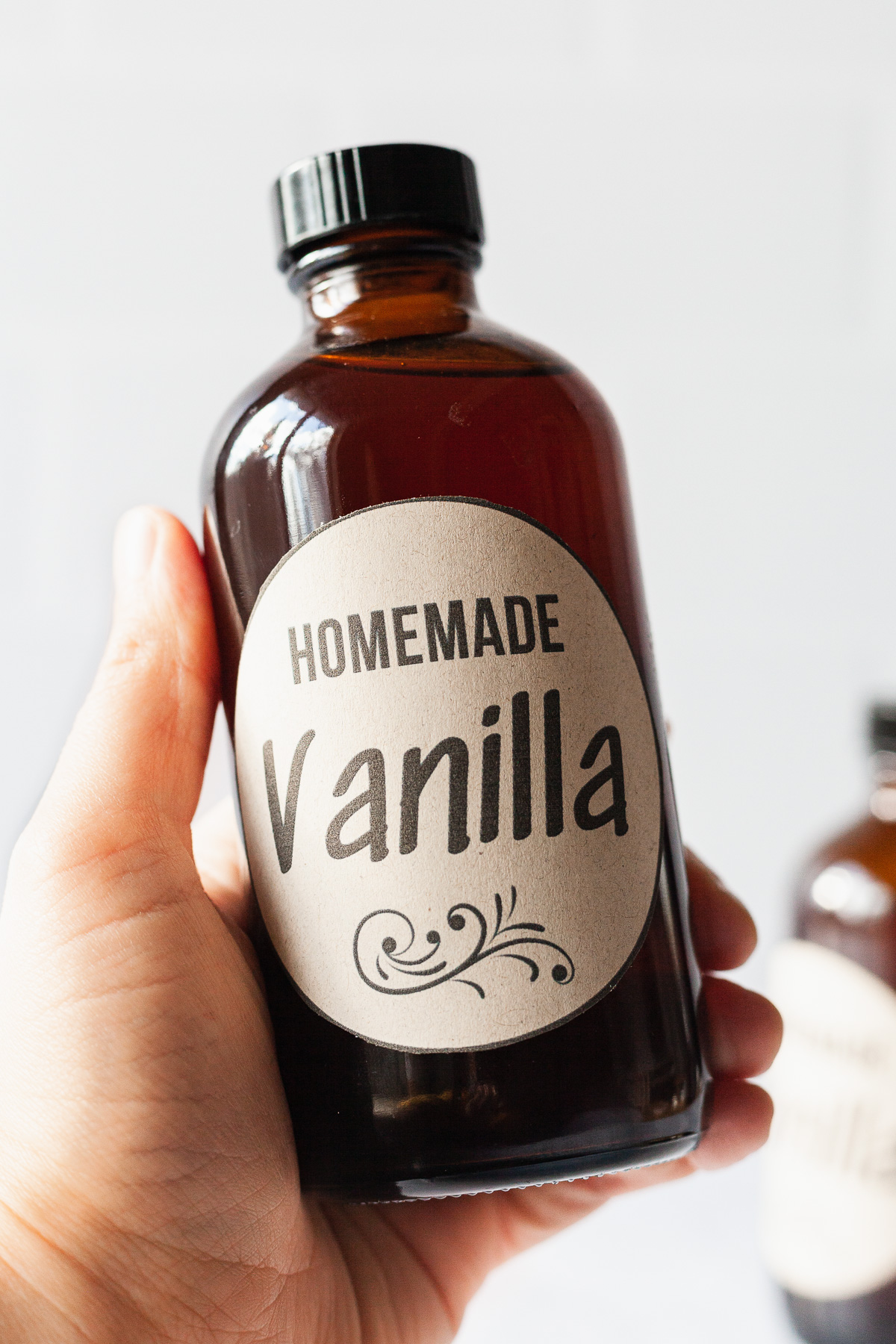 image of homemade vanilla in amber glass bottle with hand holding it