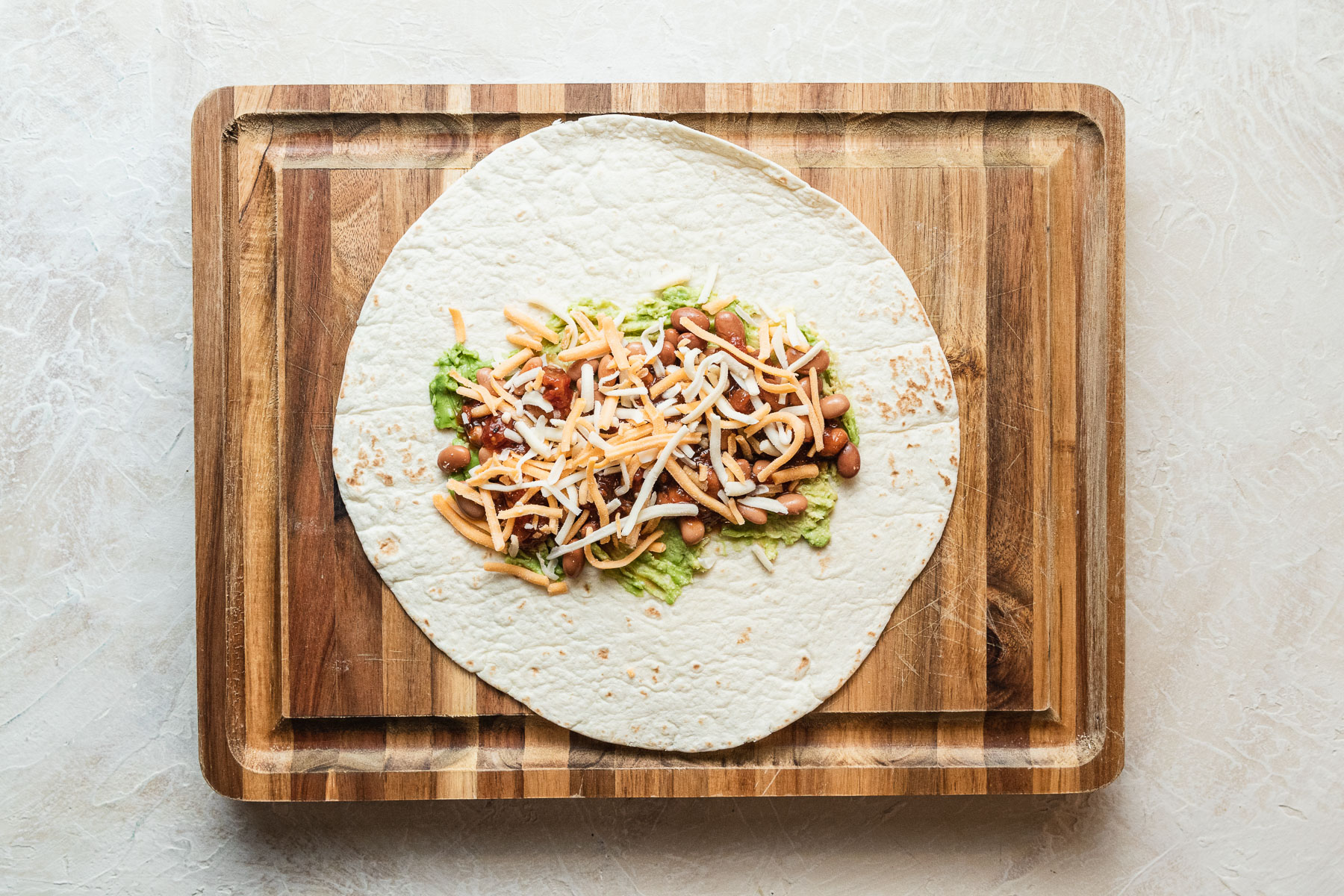 image of a grilled bean and cheese burrito open on a wood cutting board