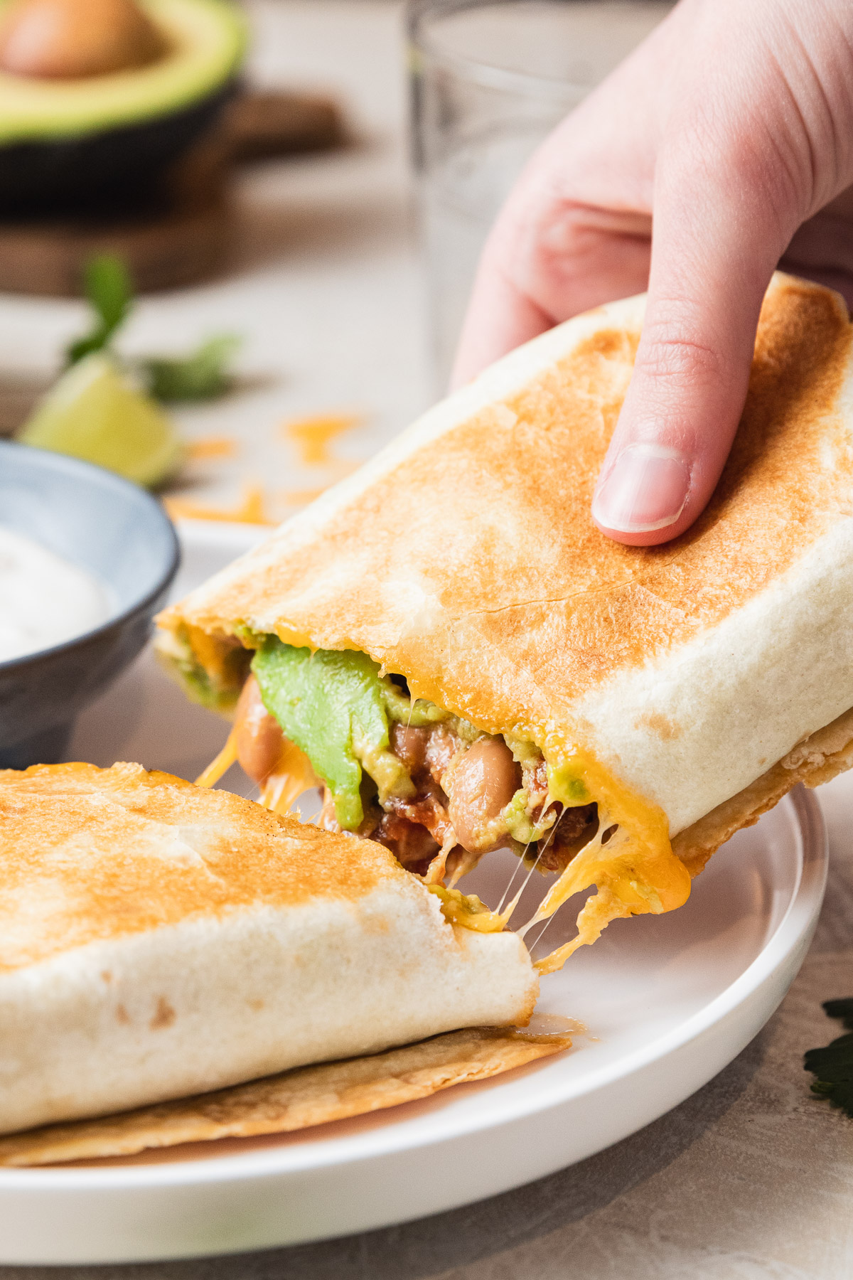 close up image of a grilled burrito cut open with a hand pulling it away from the white plate