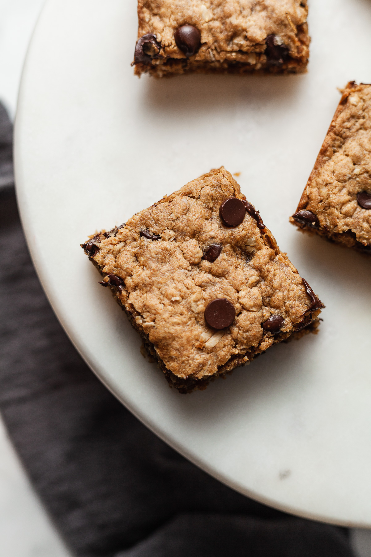top view image of three peanut butter oat bars  on white plate