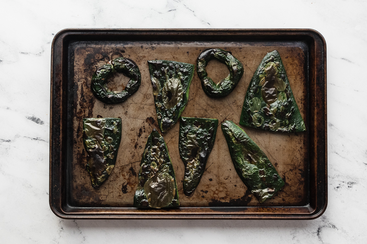 image of charred poblano peppers on baking sheet