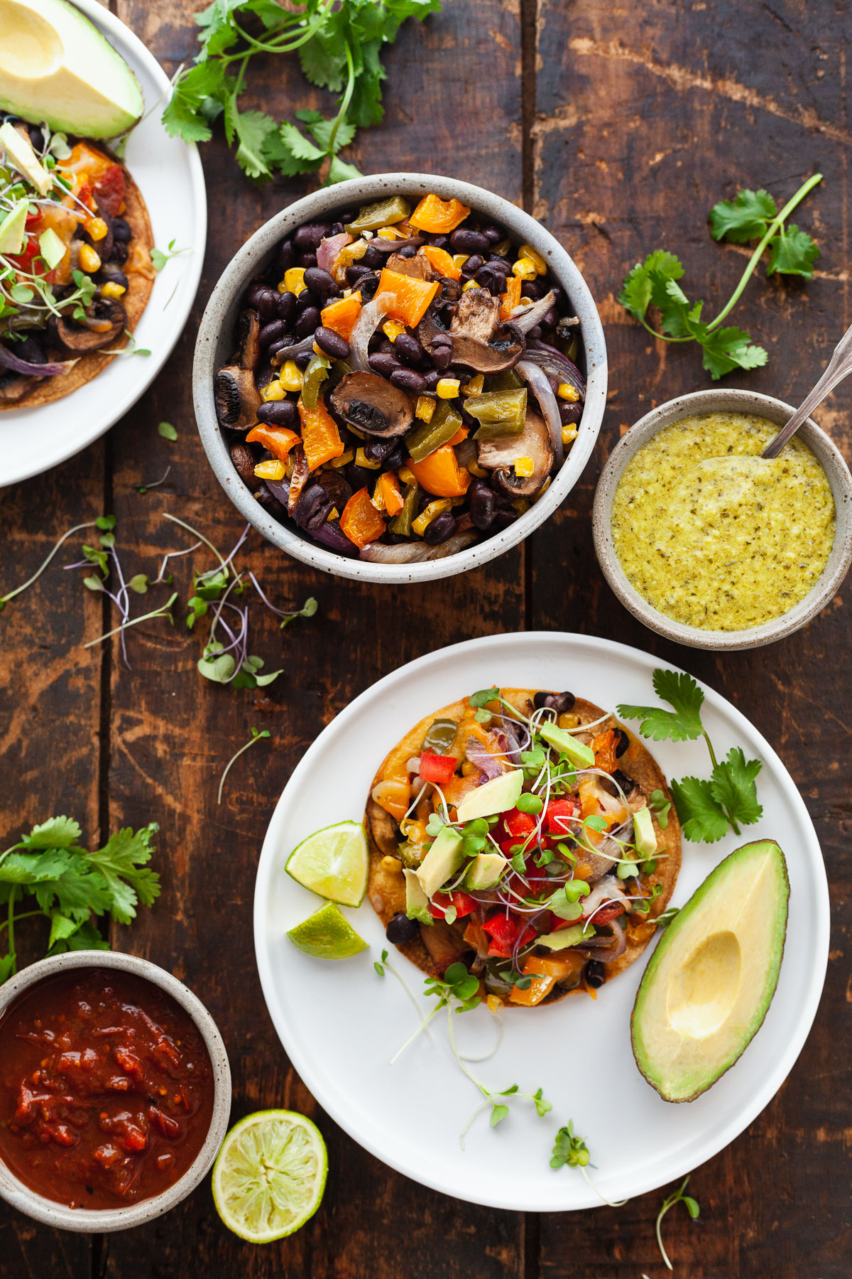 image of everything needed for roasted veggie tostadas. White plate wi.th veggie tostada and avocado. Bowls with sauce and veggies on wooden table.