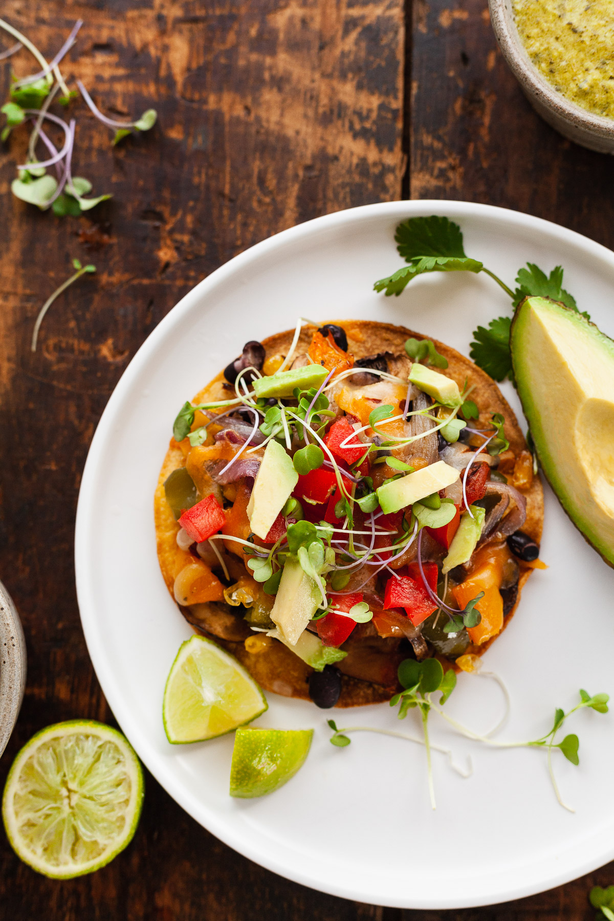 image of roasted veggie tostada on white plate with avocado and limes on wooden table
