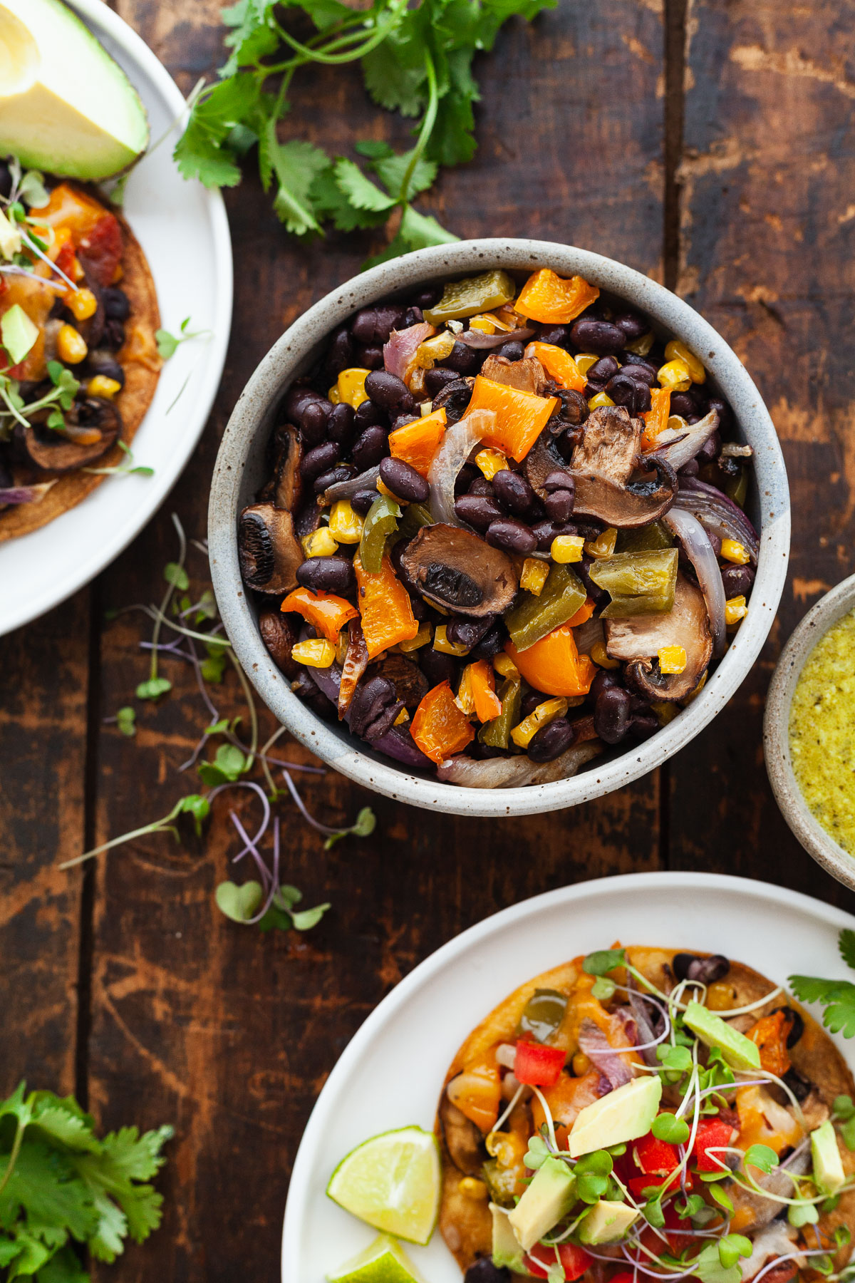 top view image of cooked veggies in bowl with roasted veggie tostadas on white plates in the corner on wooden table