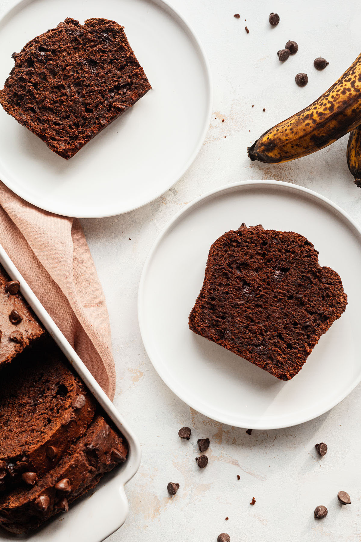 top view image of two white plates with sliced chocolate banana bread on them along with a ripe banana on table and chocolate banana bread in white pan