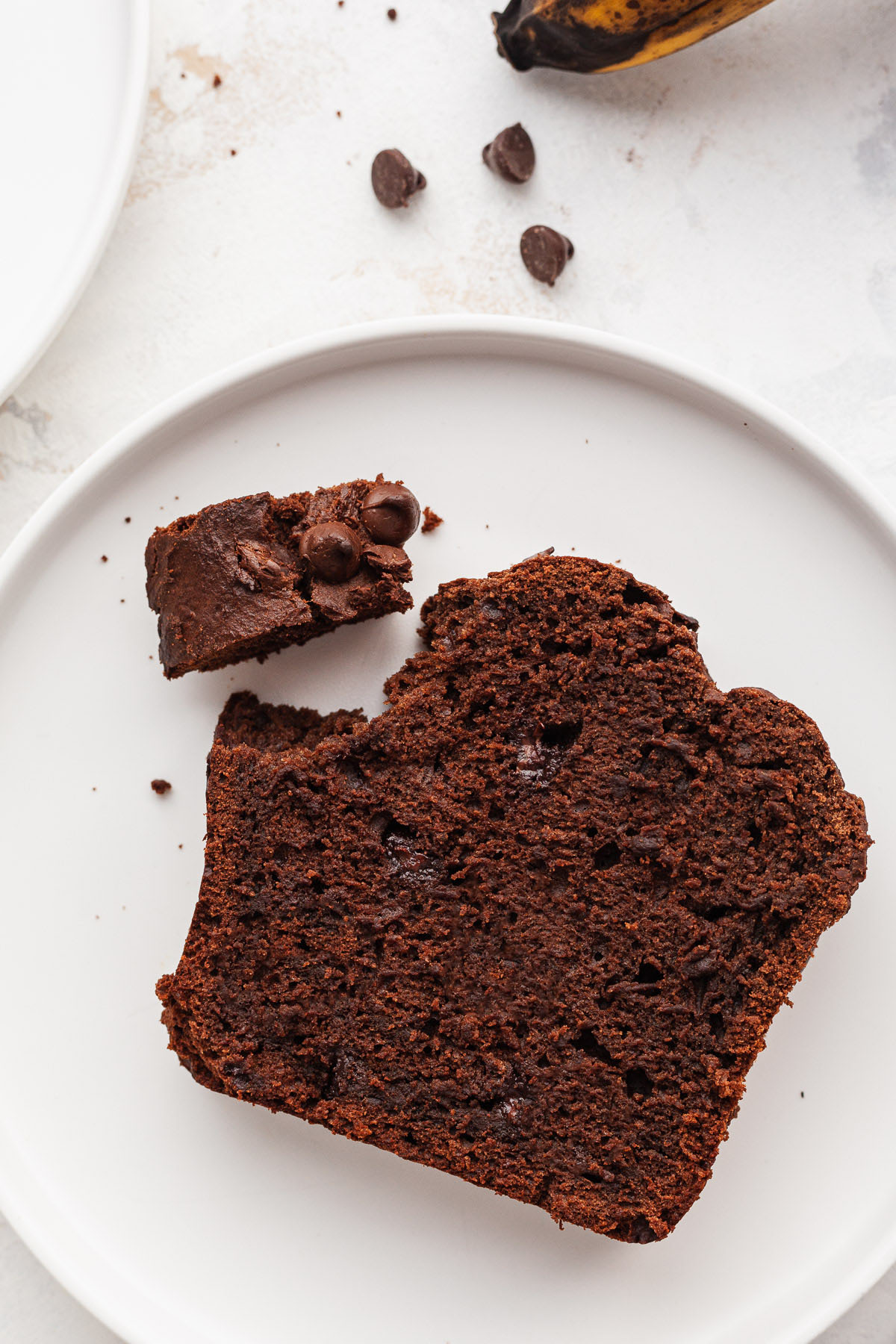 close up image of a slice of chocolate banana bread on white plate