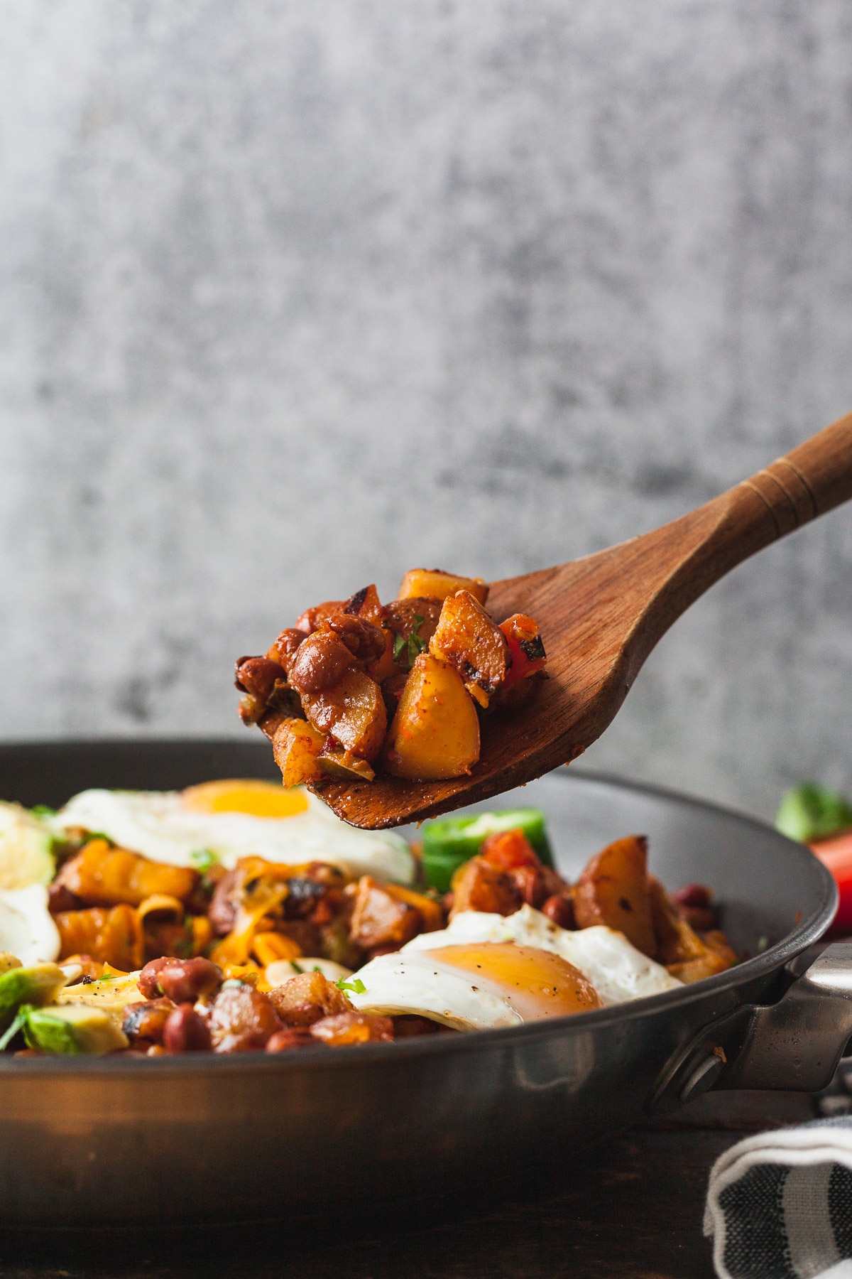 side view image of wooden spoon scooping out southwest veggie breakfast in pan