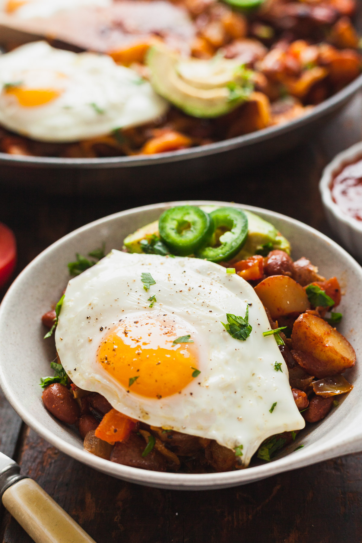 close up image of southwest veggie breakfast skillet in white bowl with pan of veggie breakfast skilllet in background