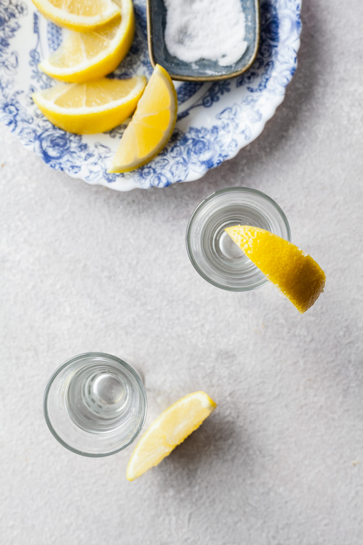 top view image of two shot glasses with vodka and lemon wedges. Plate of lemons and sugar.