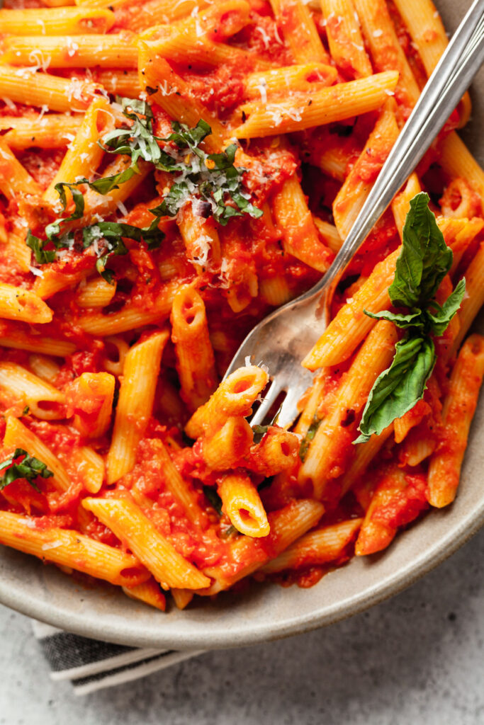 a fork and plate of penne with tomato sauce and basil
