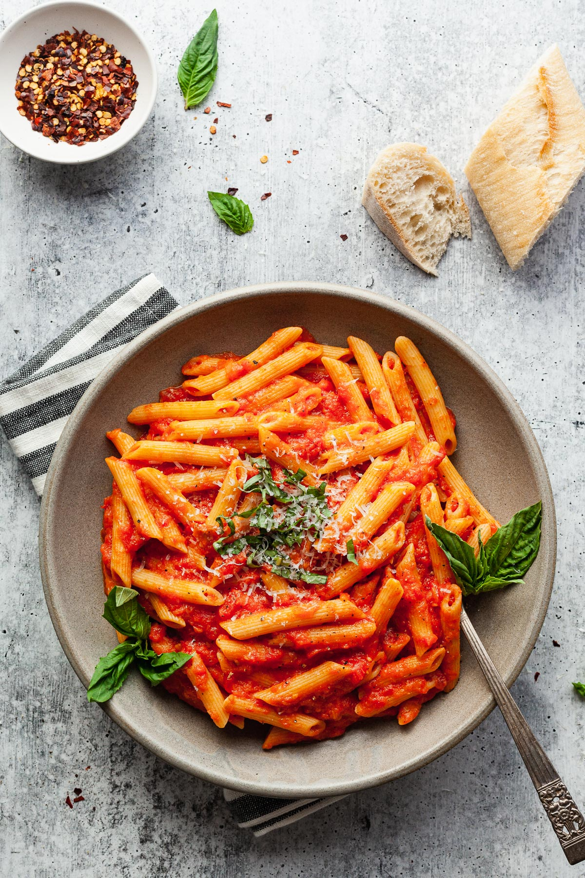 a plate of penne pomodoro with a fork, napkin, bread, and crushed red pepper flakes