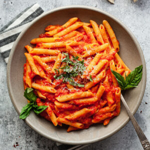 a plate of penne al pomodoro with basil and a fork