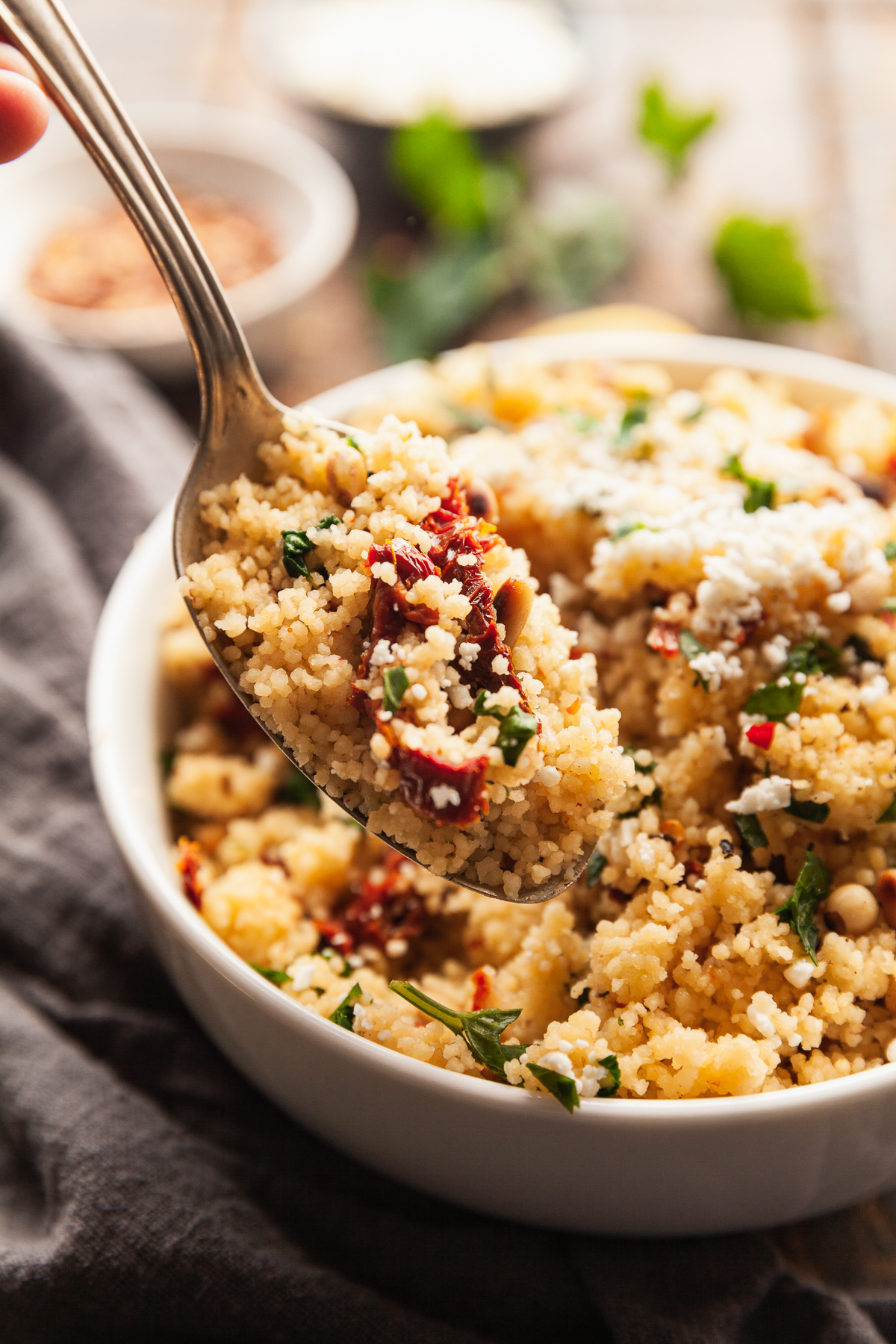 a spoon scooping out mediterranean couscous salad from a white bowl