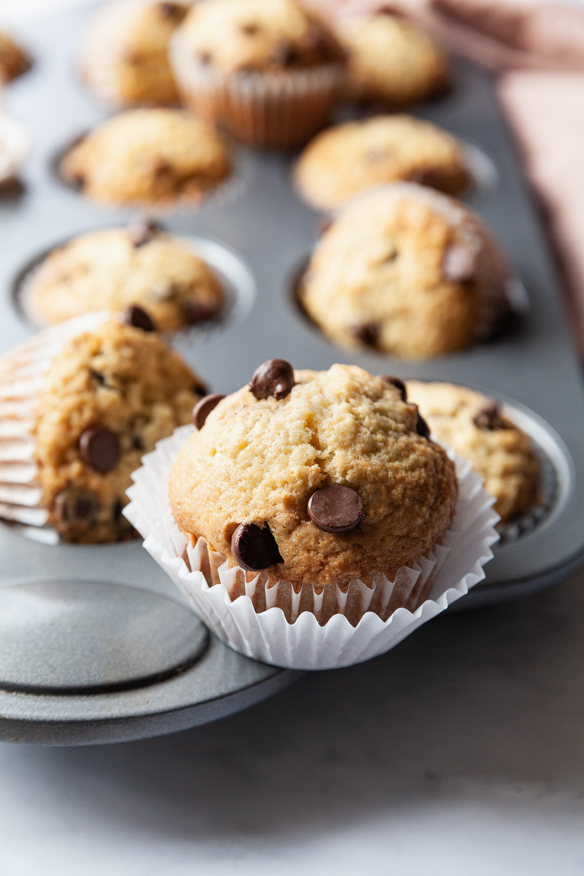 the best chocolate chip muffins with white liners on a muffin tray