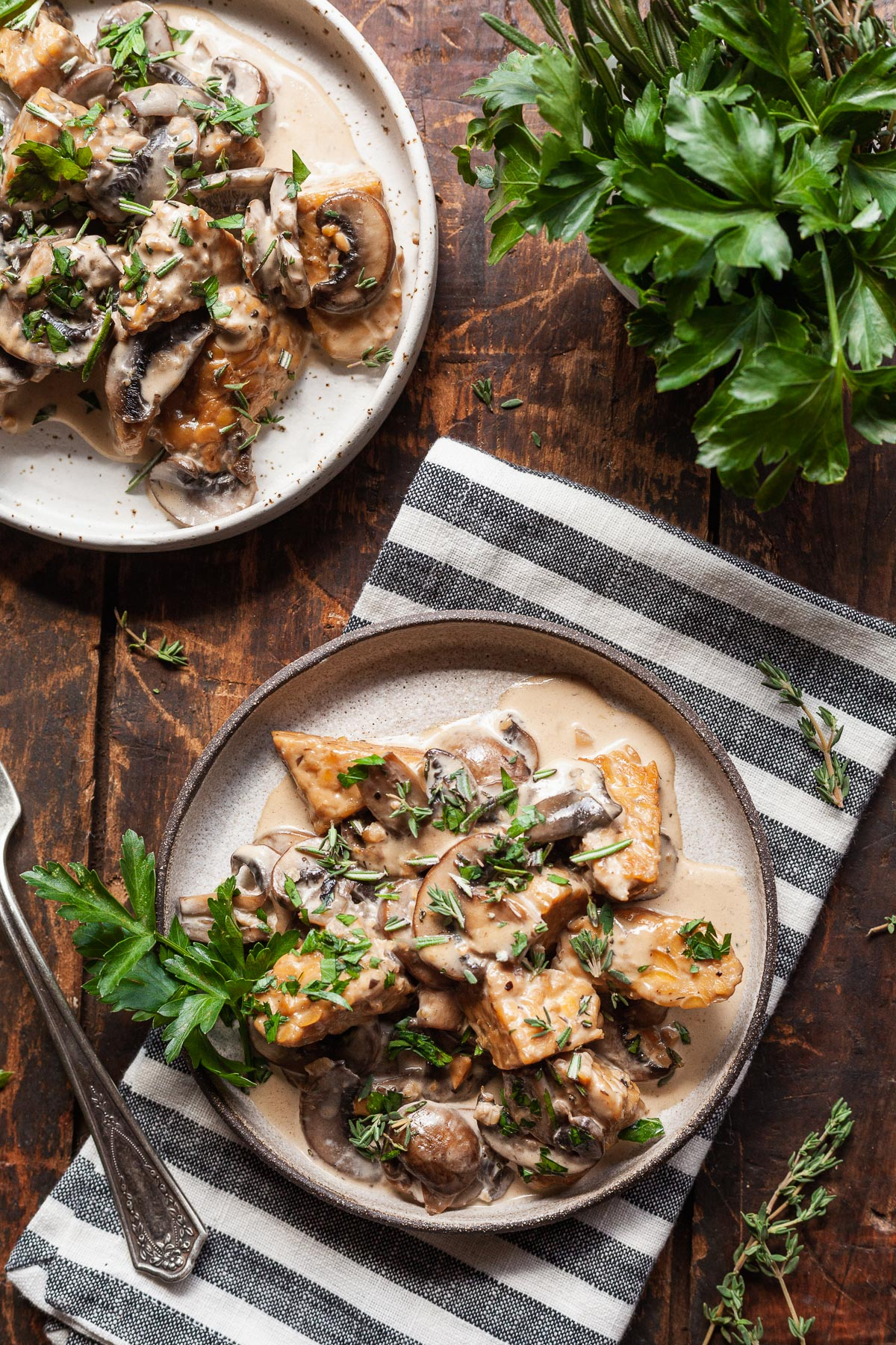 two plates of tempeh with creamy mushroom sauce with a napkin and herbs