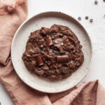a single serve vegan chocolate brownie cookie on a plate with a pink napkin