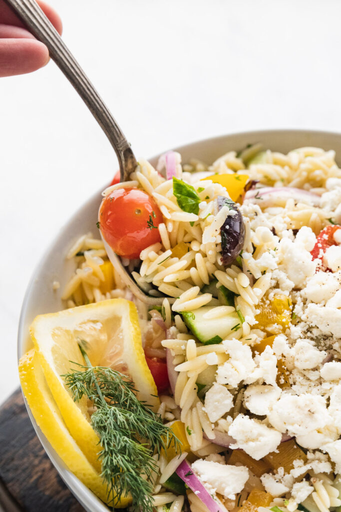 a spoon dishing out some greek orzo pasta salad from a bowl