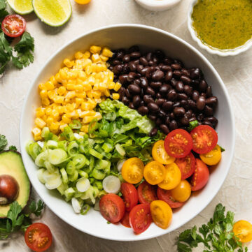 southwest salad ingredients in a white bowl with other veggies around