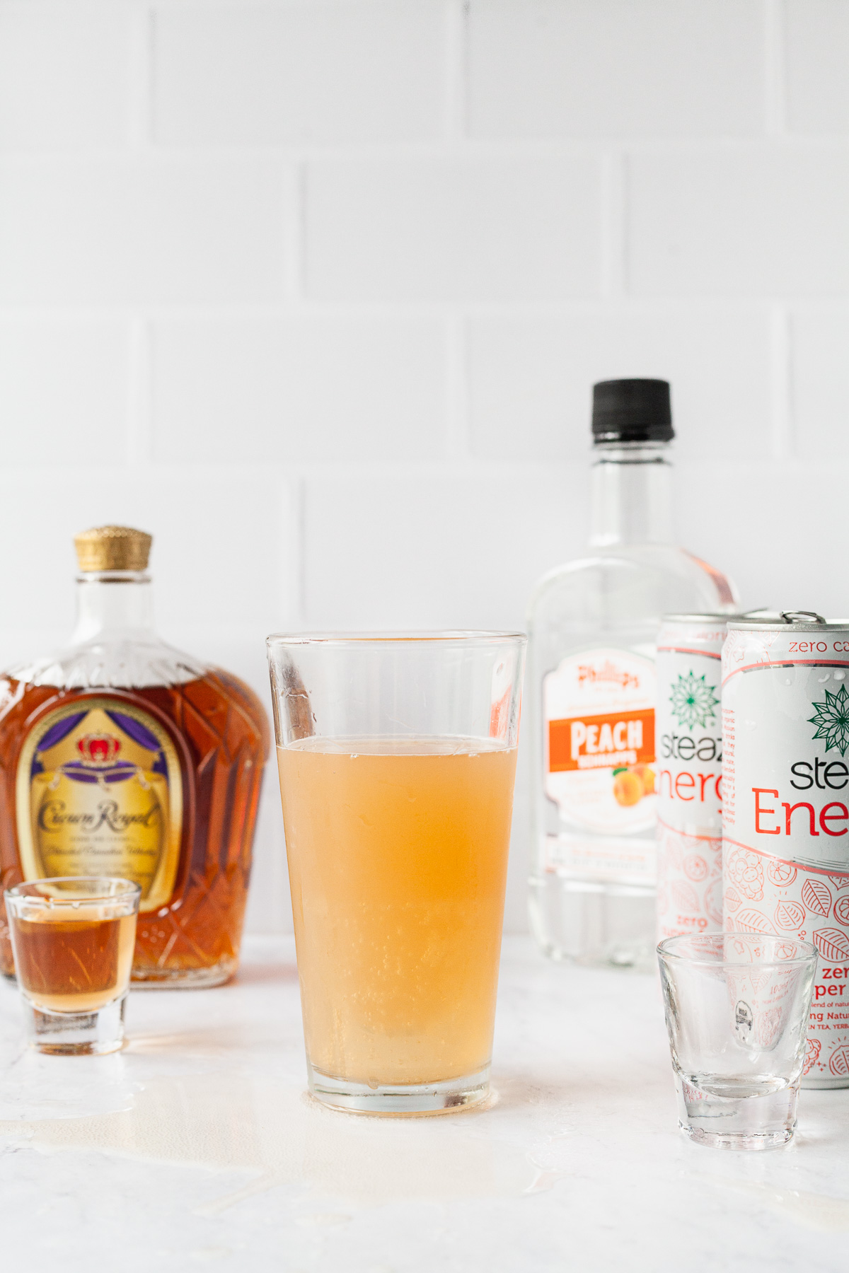 a yellow orange drink of a vegas bomb in a tall pint glass on a white counter with other liquors and shot glasses