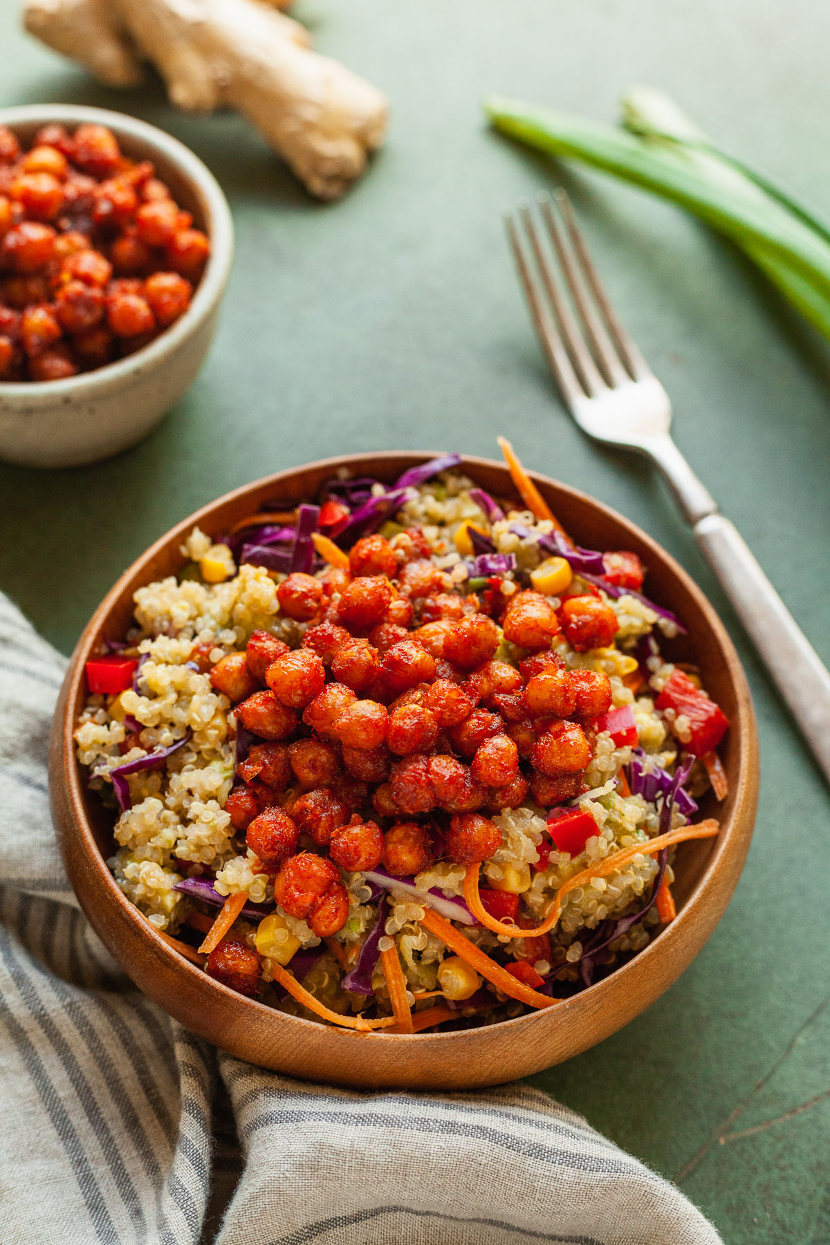a bowl of the best quinoa salad with a fork, napkin, and veggies