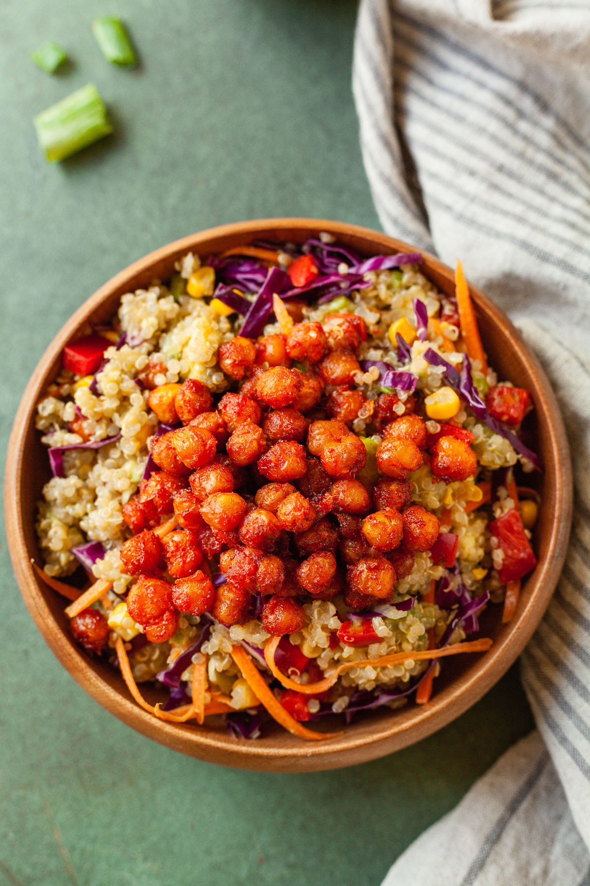 a bowl of vegan quinoa salad on a green table with a napkin