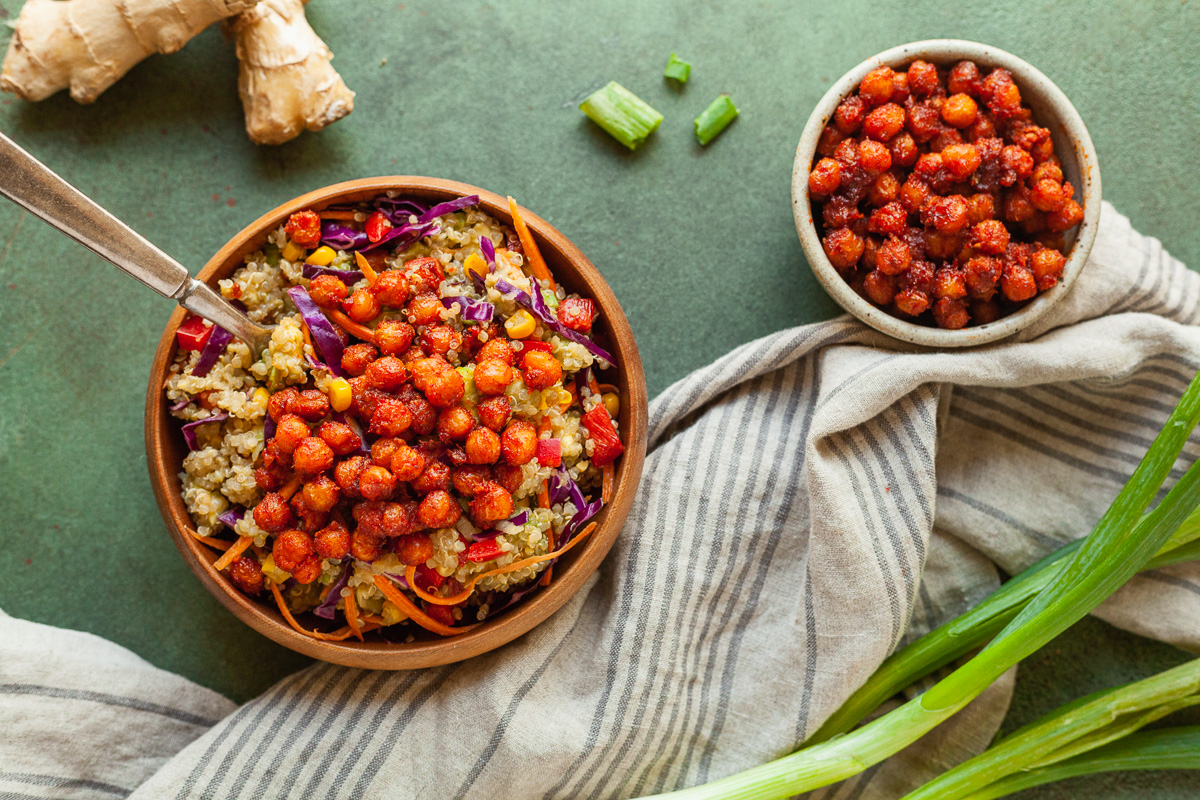 a bowl of rainbow quinoa salad and a bowl of gochujang chickpeas on a green table with veggies and a towel