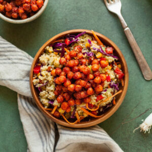 a bowl of rainbow quinoa salad with a linen napkin and fork