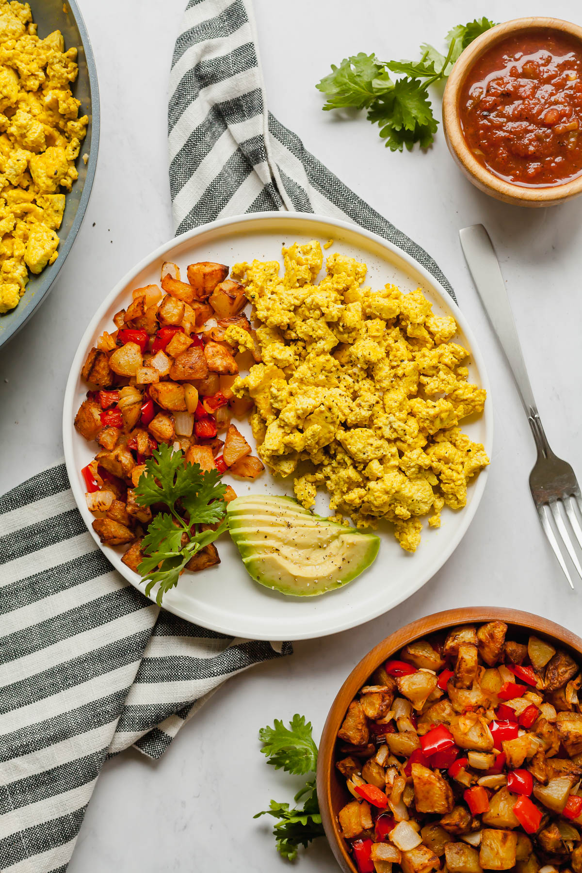 air fryer american fries on a white plate with scrambled tofu and avocado on a white table with a striped towel