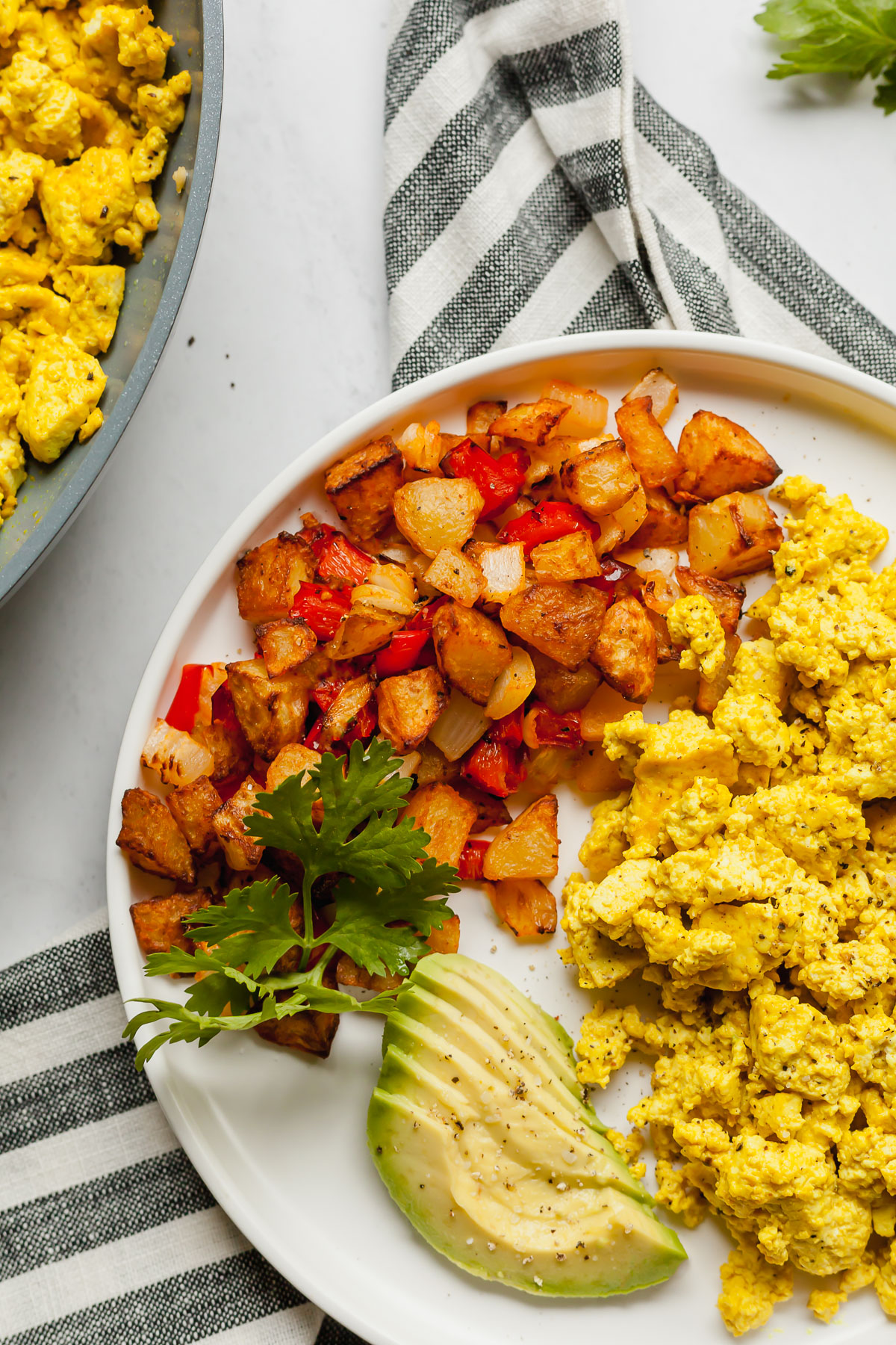 a white plate with air fryer cottage fries, avocado, and scrambled tofu