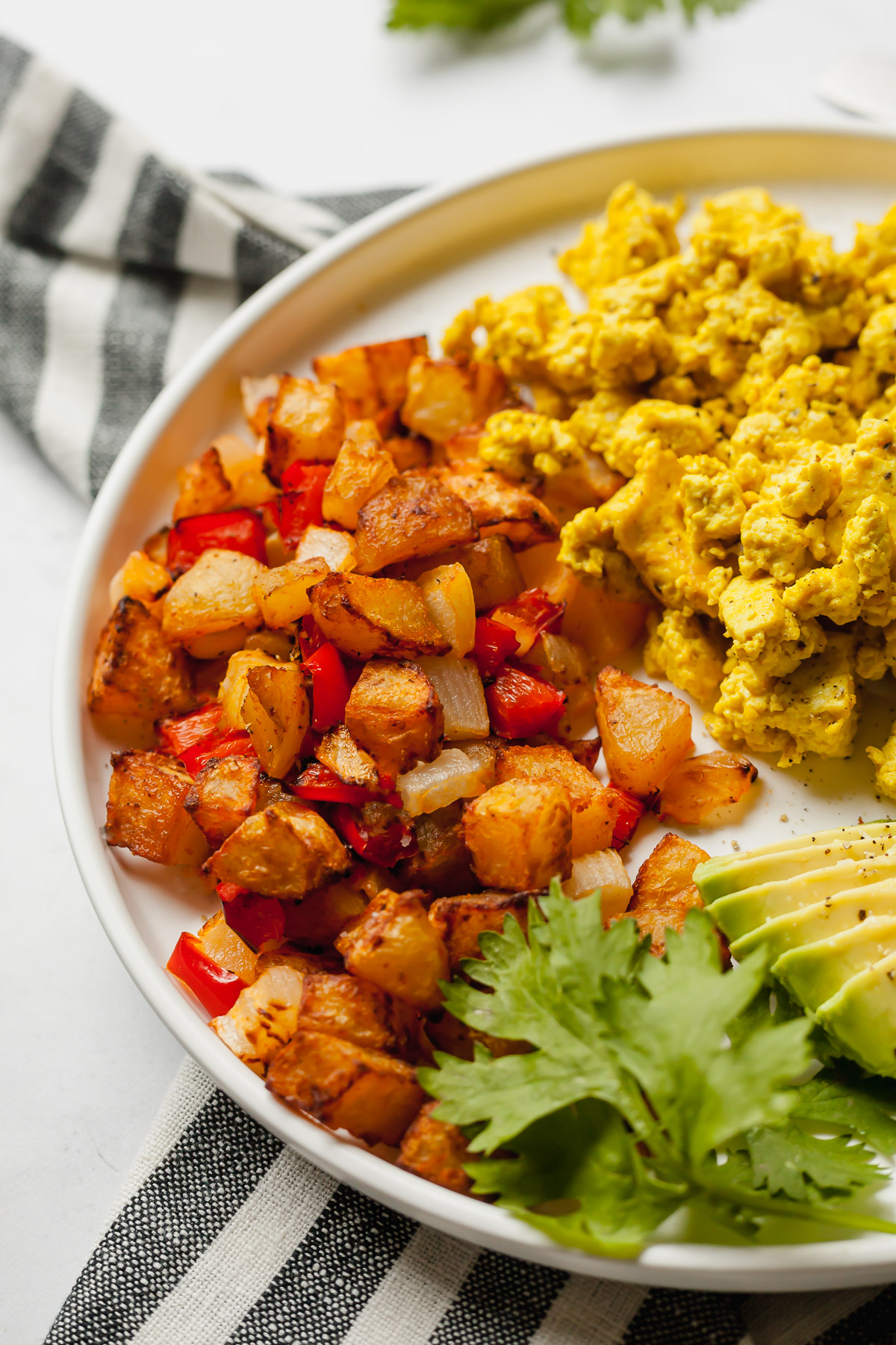 air fryer breakfast potatoes on a white plate with avocado and scrambled tofu