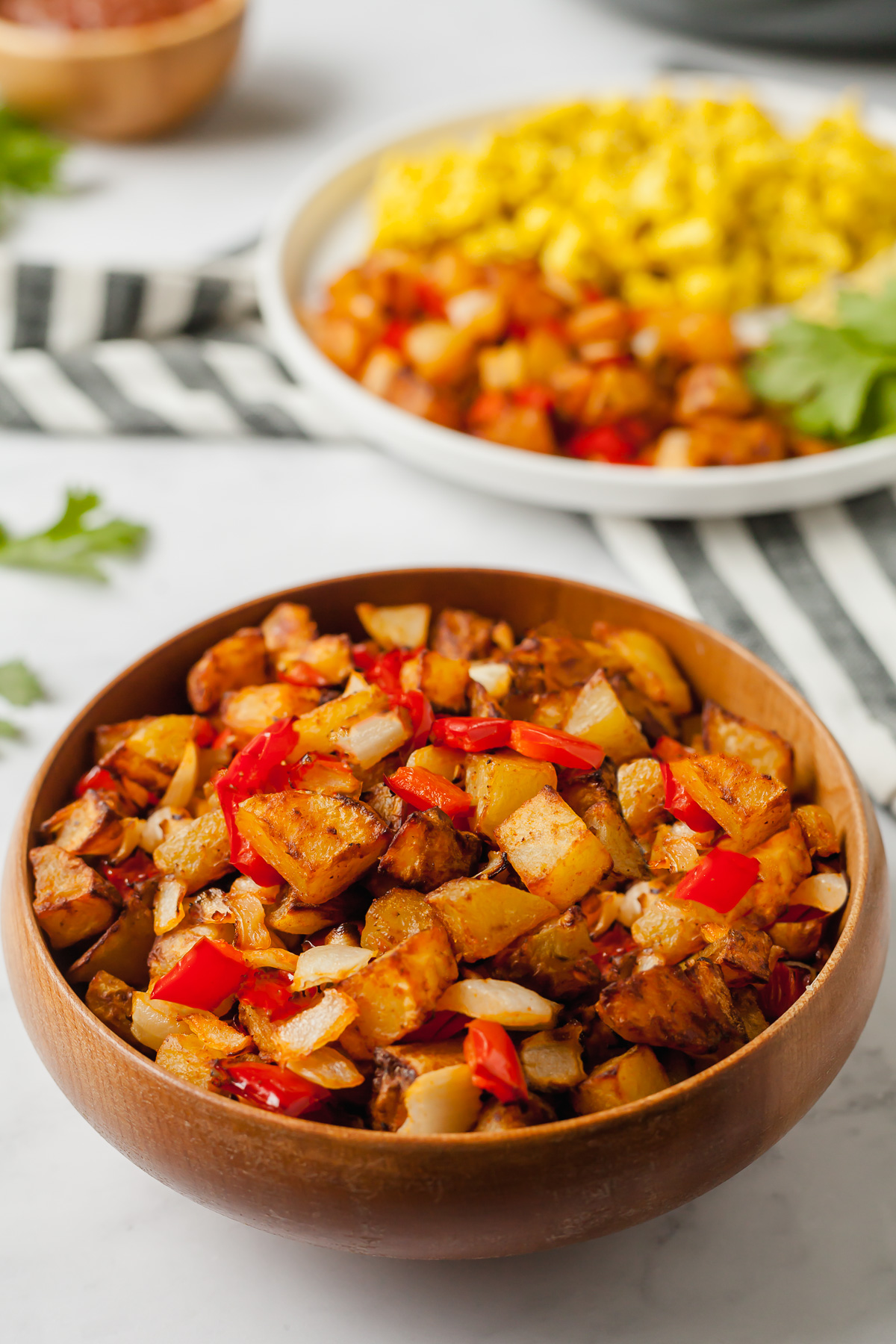 a bowl of air fryer home fries with more food in the background
