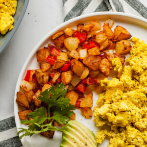 air fryer home fries on a plate with avocado and scrambled tofu