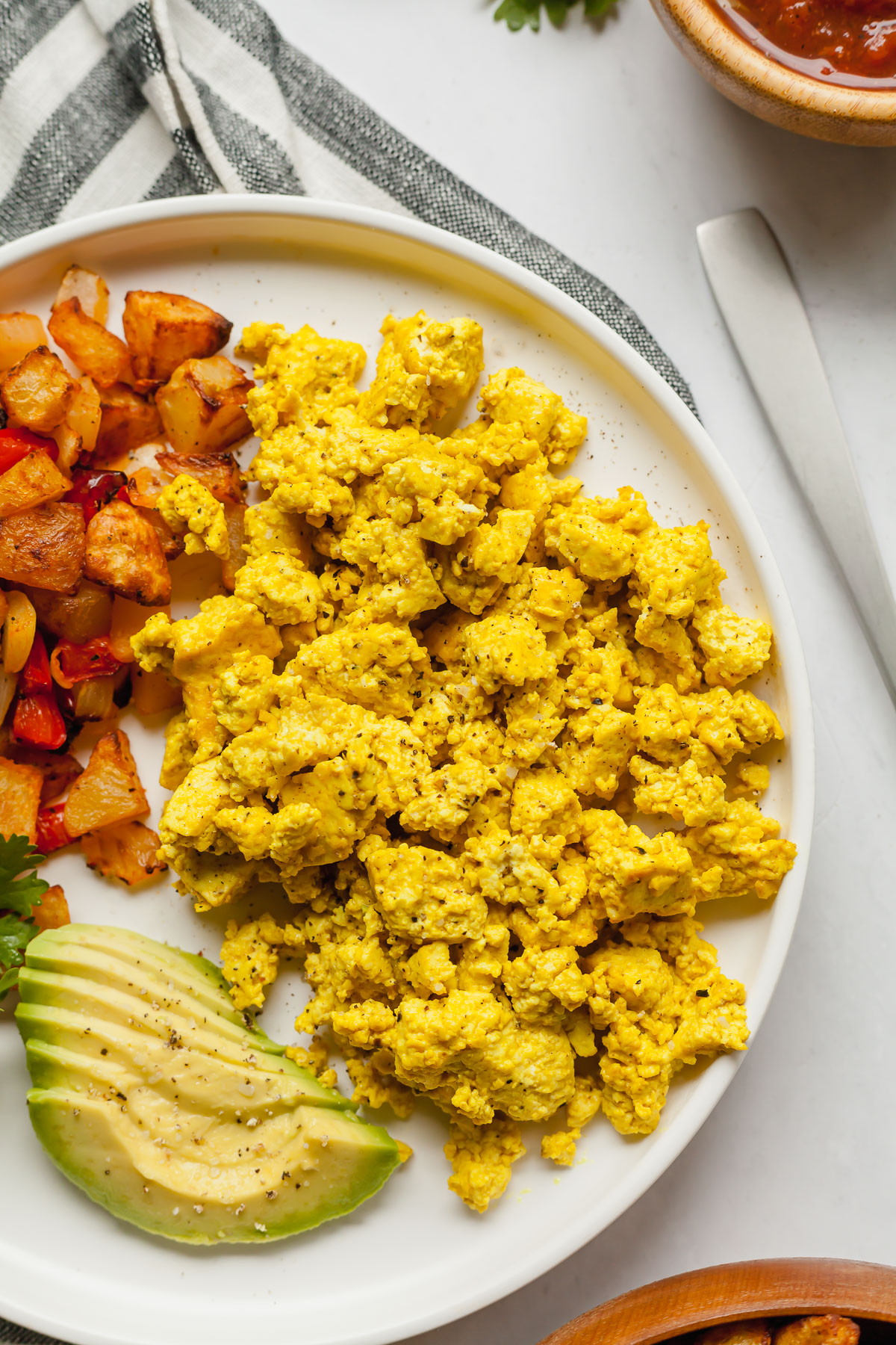 vegan tofu eggs on a white plate with home fries and avocado slices