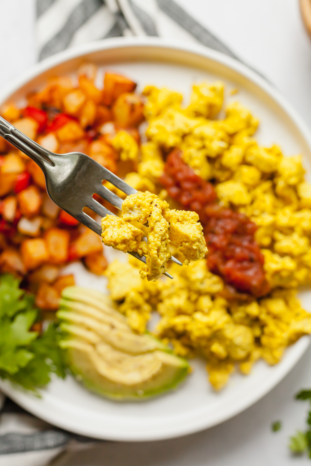 tofu scrambled eggs on a fork above a plate of more scrambled tofu, home fries, and avocado slices