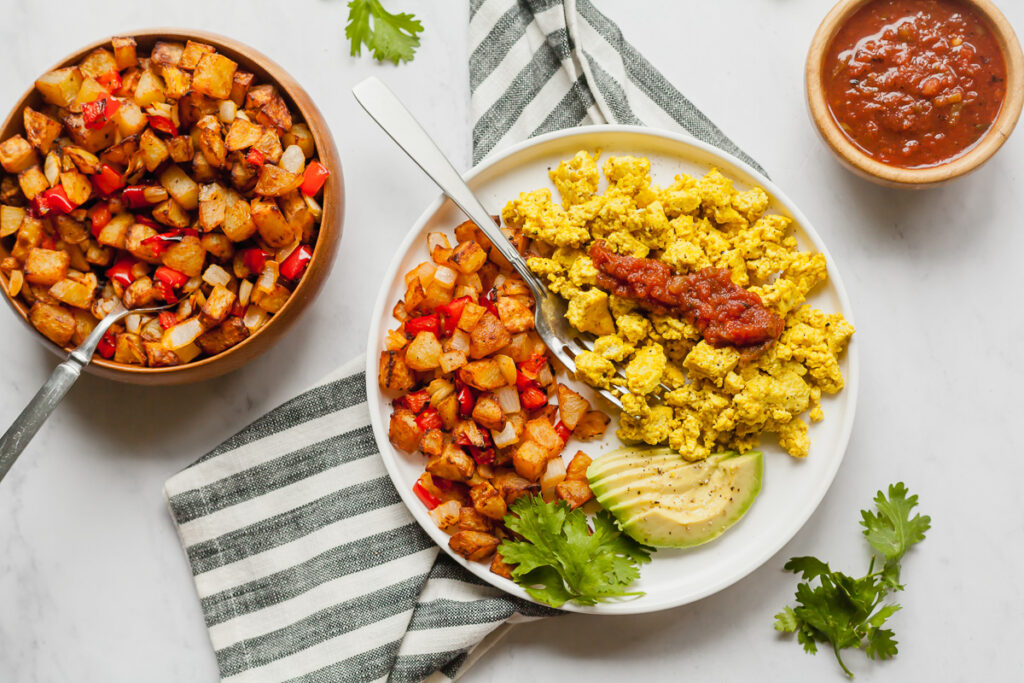 tofu breakfast scramble on a white plate with home fries and avocado slices