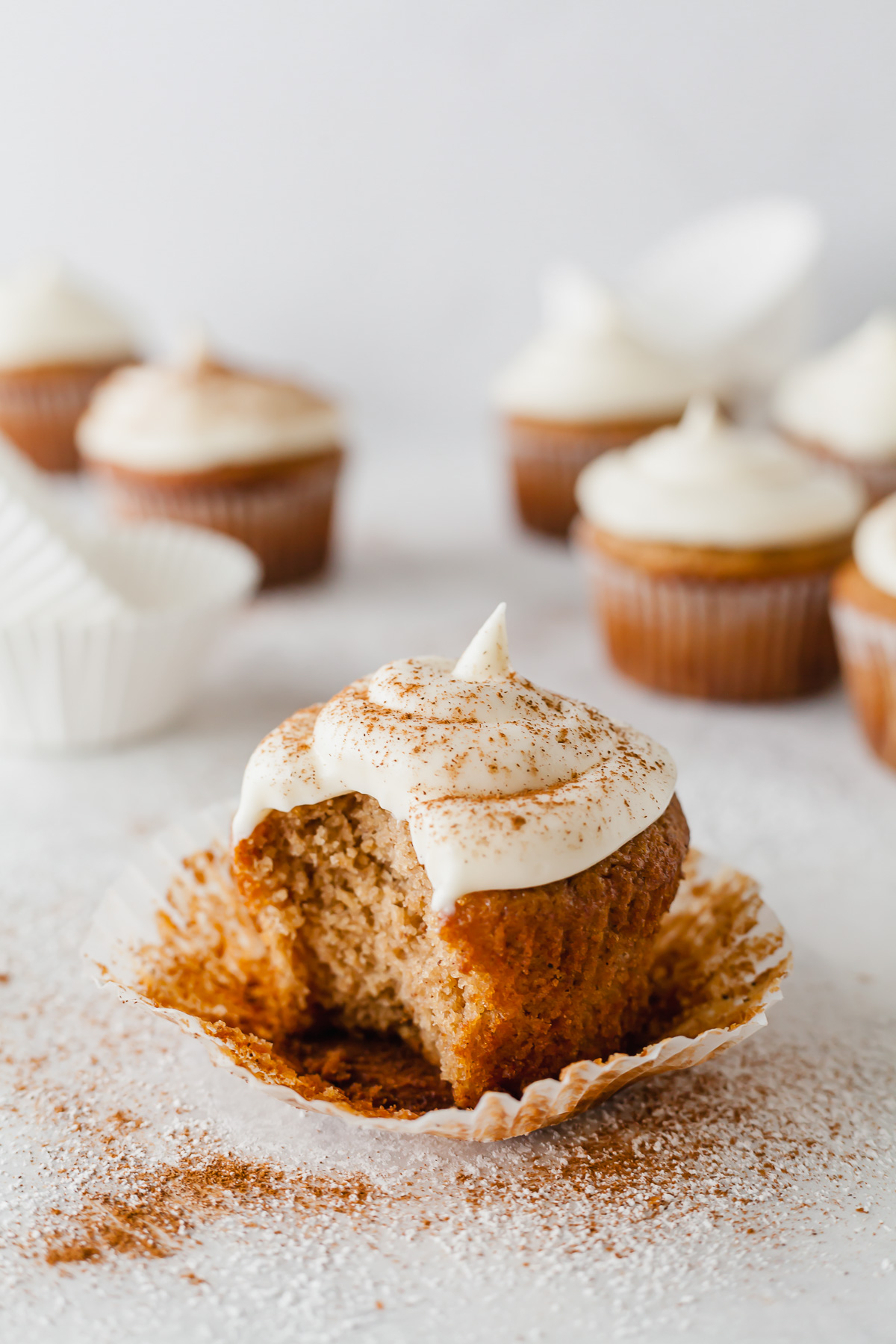 an applesauce spice cupcake sitting on the paper liner with a bite taken out and a few more cupcakes in the background