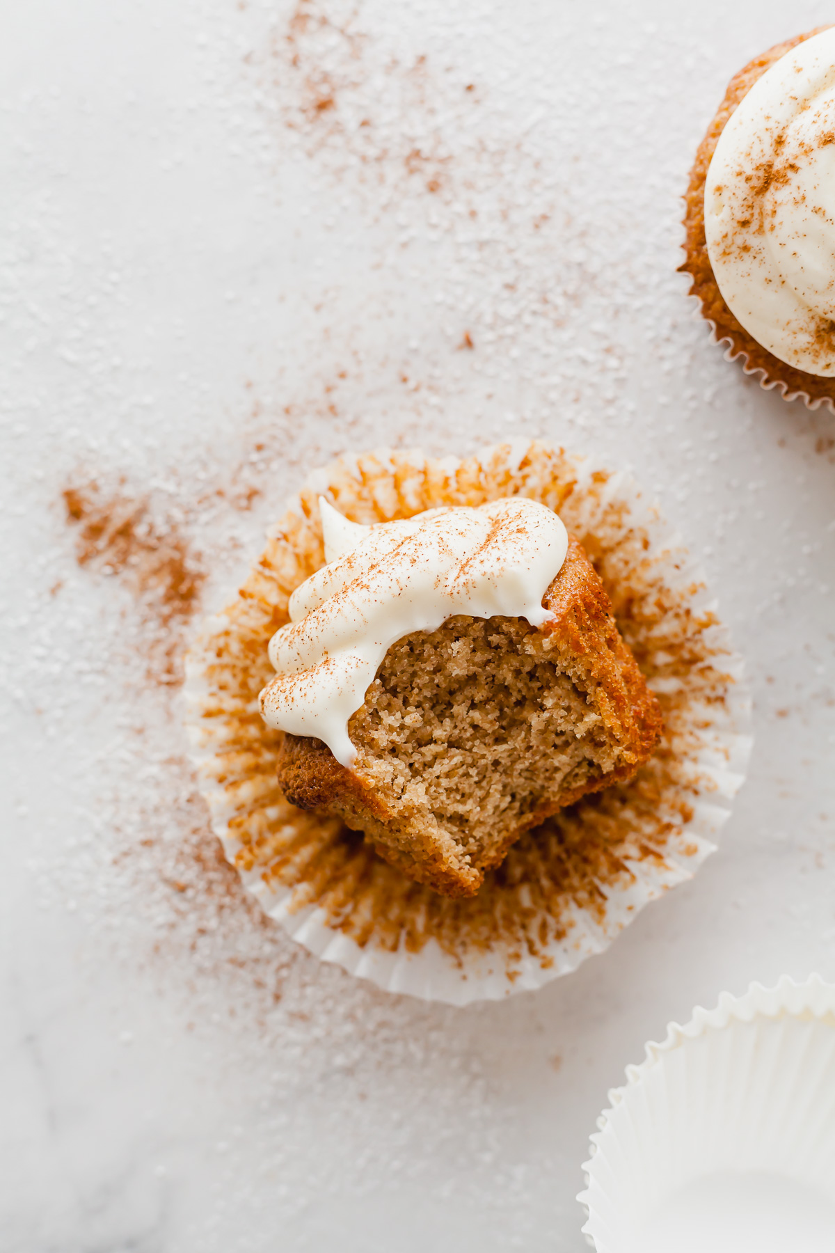 an applesauce cupcake laying on its side in the wrapper with a bite taken out