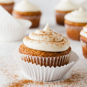 an applesauce cupcake topped with cream cheese frosting and cinnamon with more cupcakes in the background