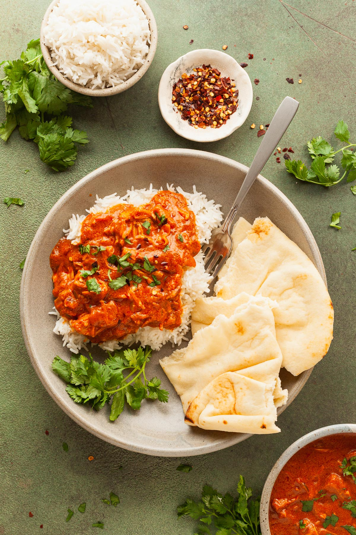 a plate of rice, naan, and vegan butter chicken on a green table with a fork