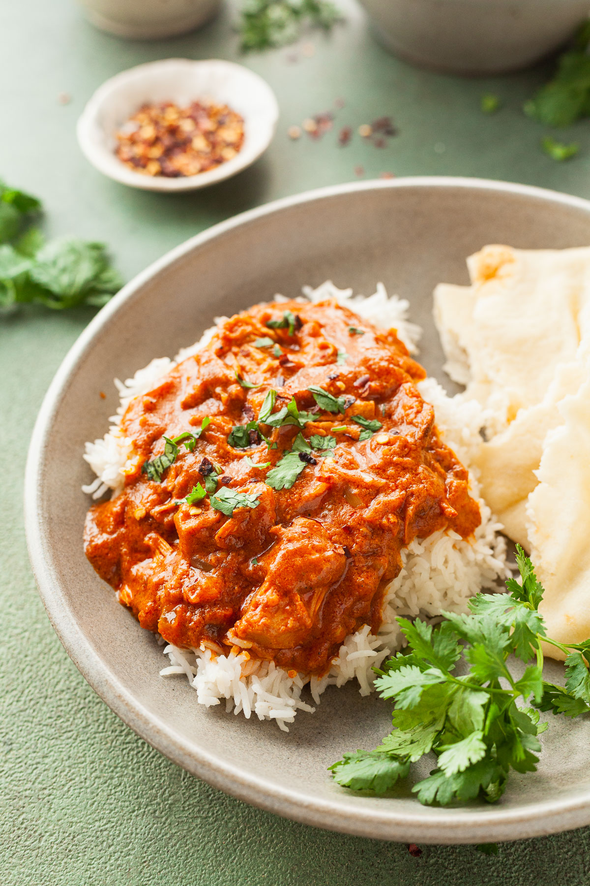 a plate with rice, naan and crock pot vegan butter chicken