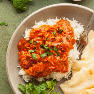 a plate of vegan butter chicken with rice and naan