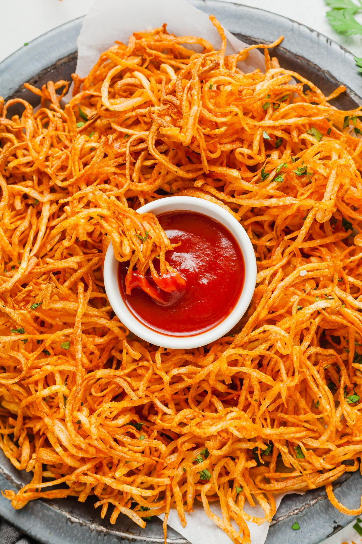 a plate of shoestring fries with a dish of ketchup in the middle