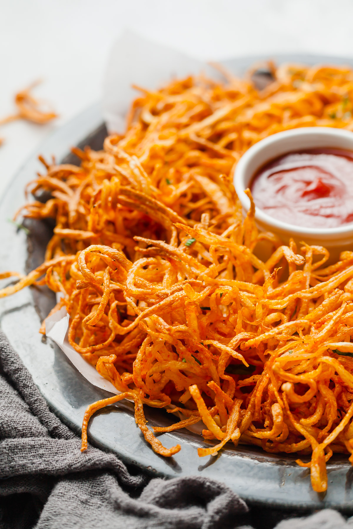a plate of shoestring french fries with a small dish of ketchup