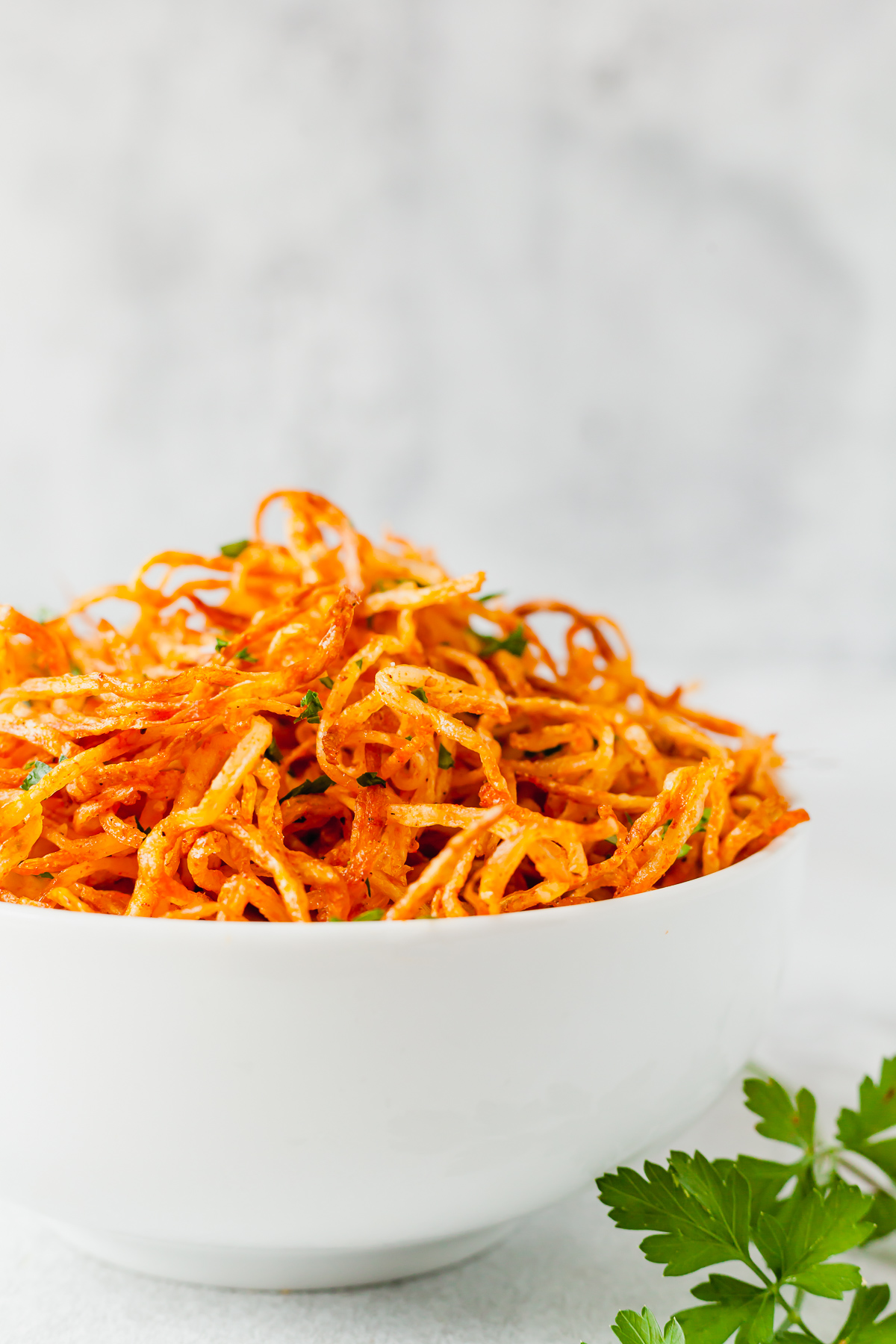 close up photo of shoestring fries in a white bowl