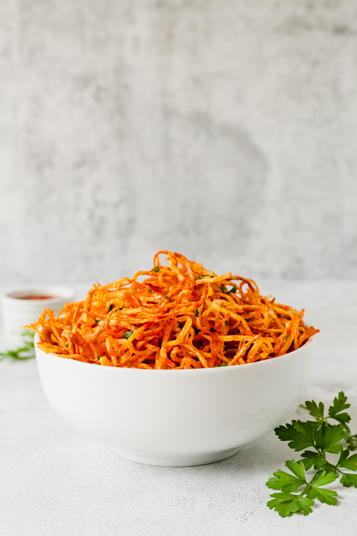 a white bowl of shoestring fries