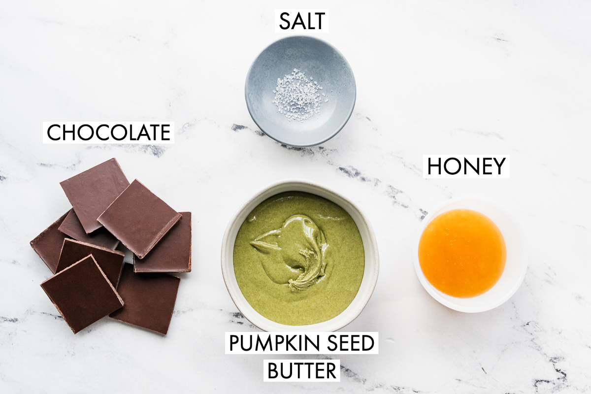 ingredients needed to make pumpkin seed butter cups including salt, chocolate, honey, and green pumpkin seed butter