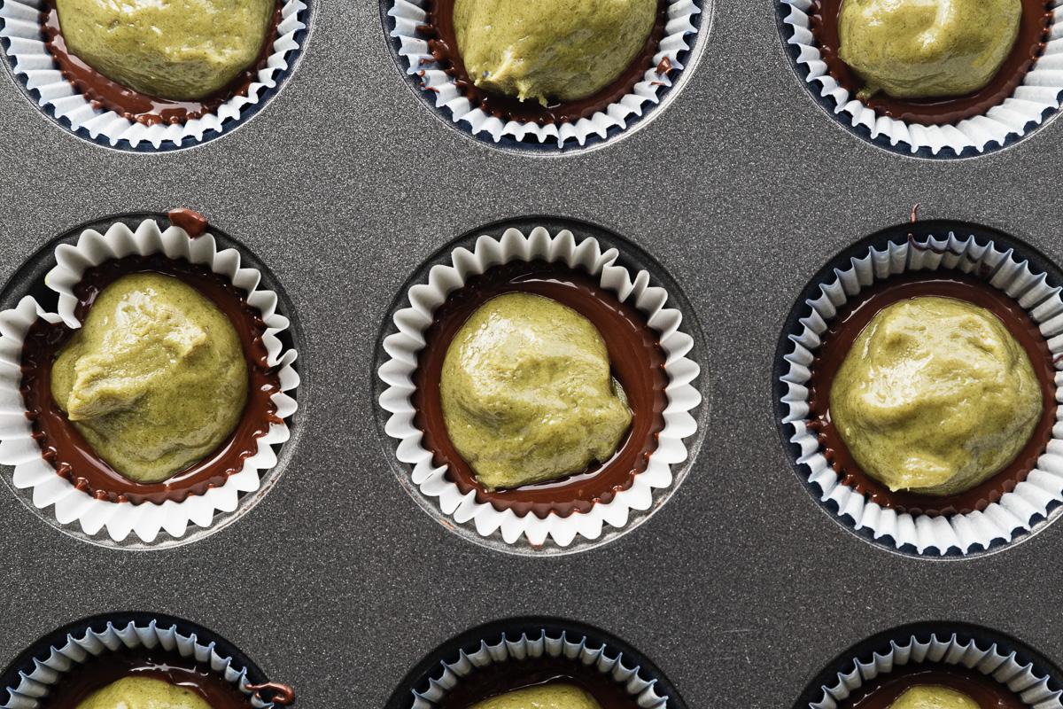 a close up shot of pumpkin seed butter and chocolate inside a mini cupcake pan