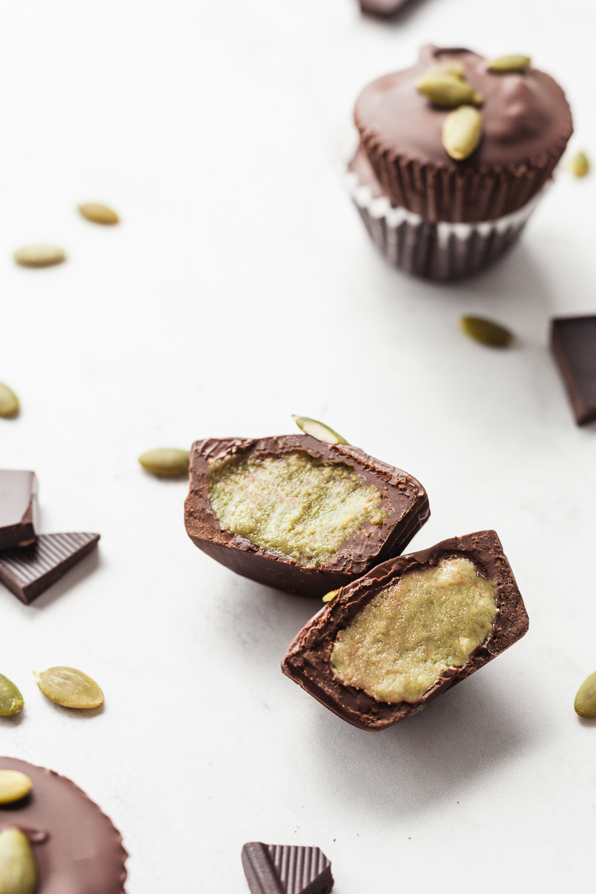 a pumpkin seed butter cup cut open showing the green inside surrounded by pumpkin seeds